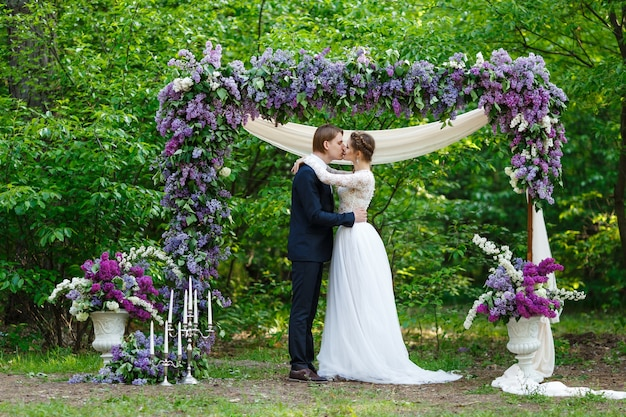 Groom and bride kissing and standing near arch with lilac flowers with vegetation background