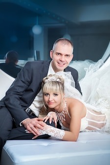 Groom and the bride lie on a bed