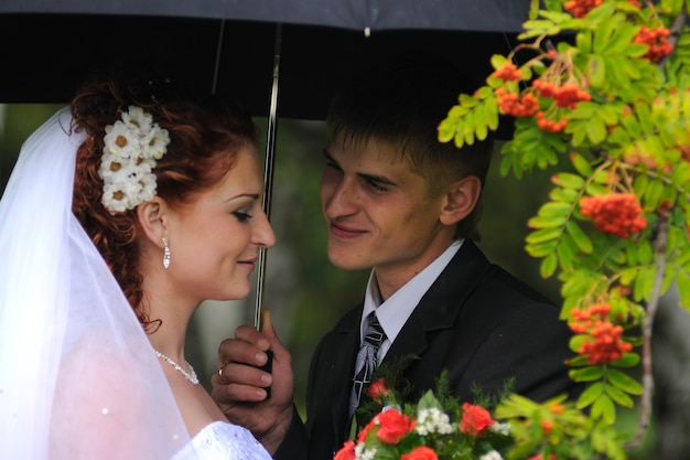 Groom and bride portrait kissing in rain