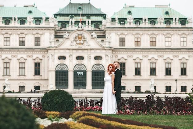 Lo sposo e la sposa in posa con uno sfondo edificio