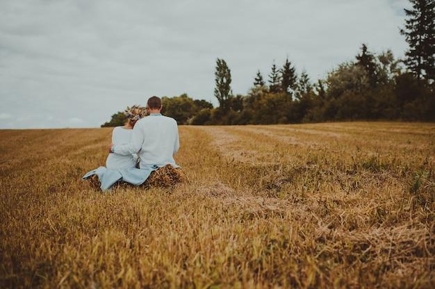 Жених невеста сидит в поле