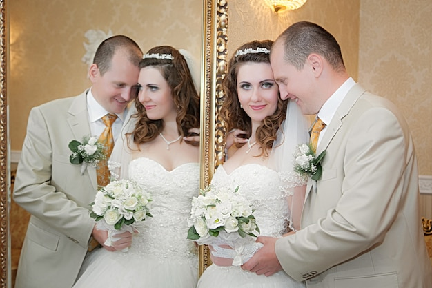 Groom and the bride stand near a mirror with a gold frame and are reflected in it