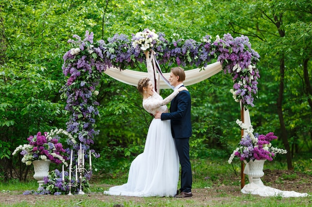 Groom and bride standing near arch with lilac flowers in vegetation background