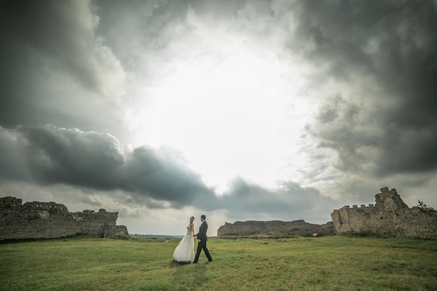 Groom and bride walking with ruins background