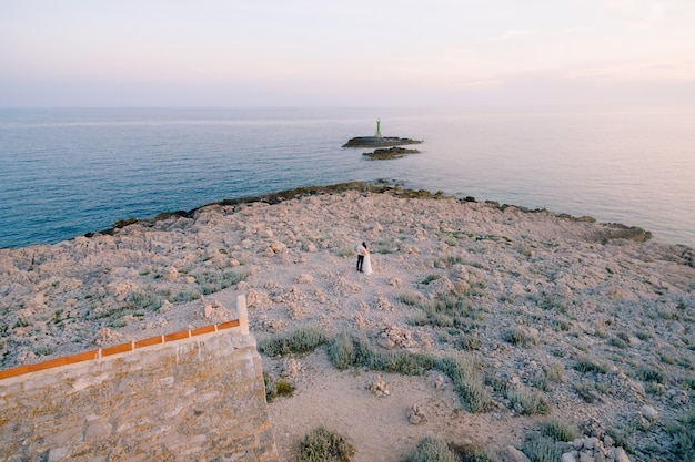 Groom and bride in a white dress stand hugging on the punta planka cape near the ancient church on