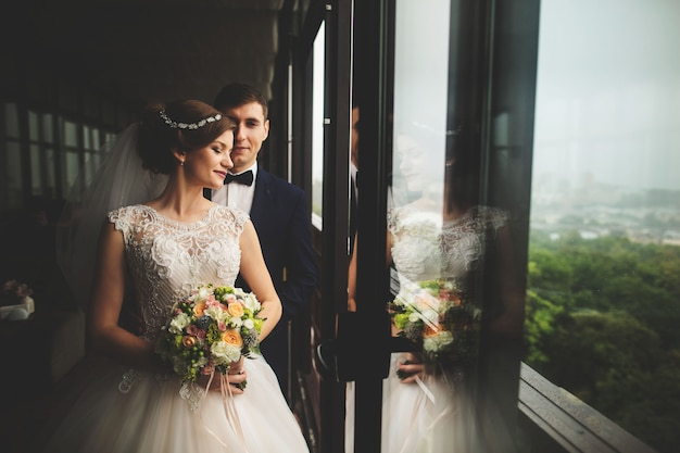 Groom and bride with a bouquet standing on terrace with green nature view