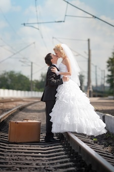 Groom and bride with a suitcase on railway rails