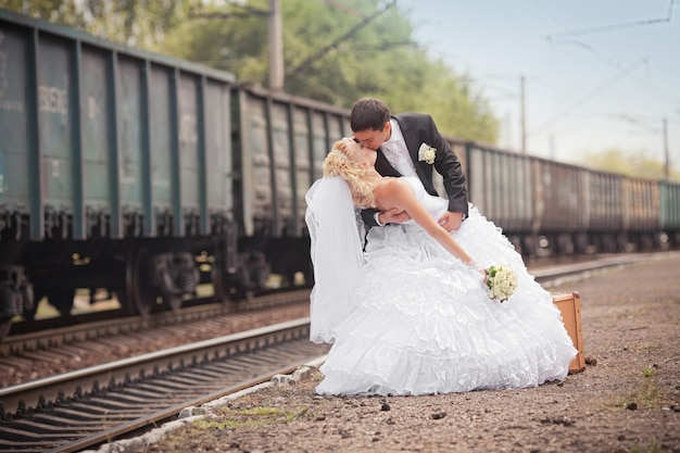 The groom and the bride with a suitcase at railway station