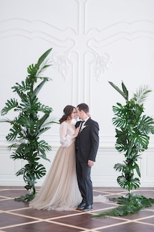 Groom and bride with wedding bouquet hold each other by hands