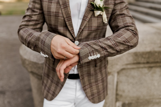 Groom in brown plaid jacket looks at his ring on the finger.