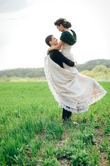 The groom in a brown suit and the bride in an ivory-colored dress on a green field receding into the distance against the sky Premium Photo