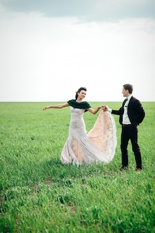 The groom in a brown suit and the bride in an ivory-colored dress on a green field receding into the distance against the sky
