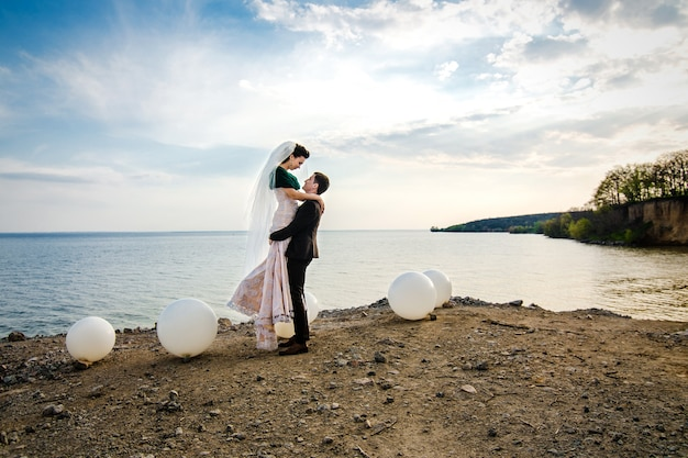 The groom in a brown suit and the bride in an ivory dress on the rocky seashore