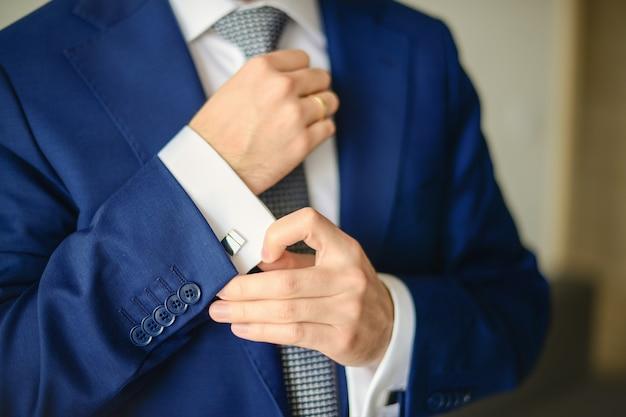Groom or businessman fasten cufflink