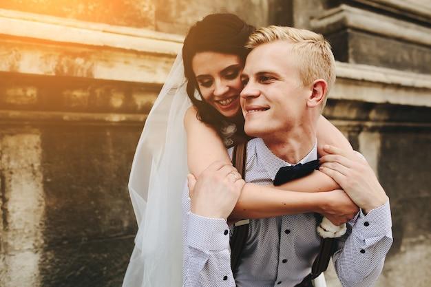 Жених несет невесту на спине, на открытом воздухе