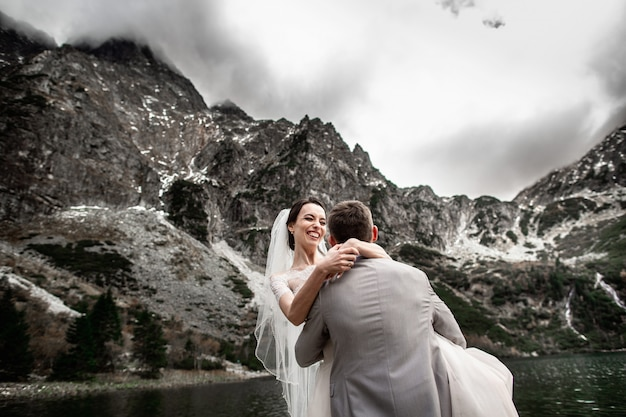 The groom circles his young bride, on the shore of the lake morskie oko. poland