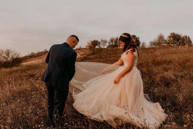 Жених очищает грязь от свадебного платья невесты посреди поля в высокой траве осенью