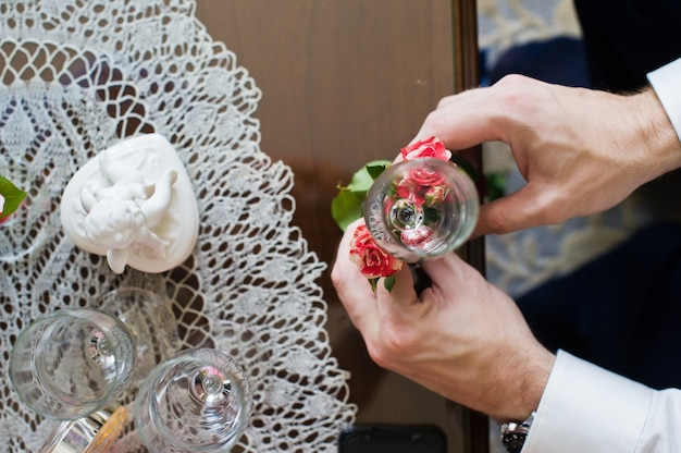 The groom decorates the wedding glasses with flowers