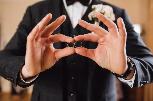 Groom demonstrates two wedding rings, without face