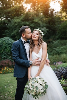 Groom dressed in a stylish suit kissing with her beautiful bride in a white wedding dress