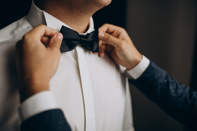 Groom dressing before the wedding ceremony, putting on a bow