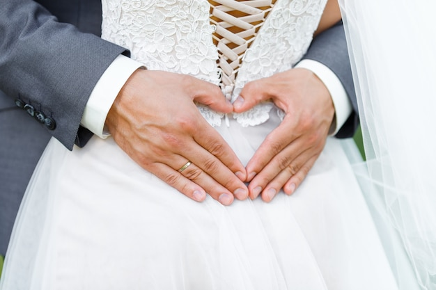 Groom embrace his bride and makes the shape of the heart from his hands with wedding ring