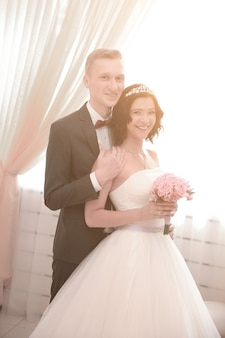 Groom embraces the bride after the wedding ceremony. photo with copy space