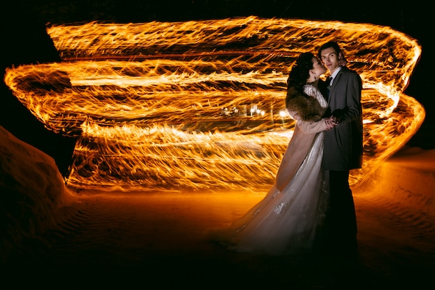 The groom embraces the bride against the background of flames, standing in the snow. technique of night photography by freezing light and lightpainting.
