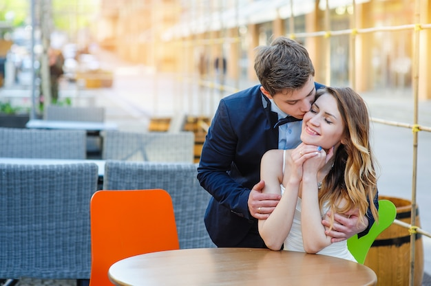 Groom embraces the bride's shoulders at a table in a cafe