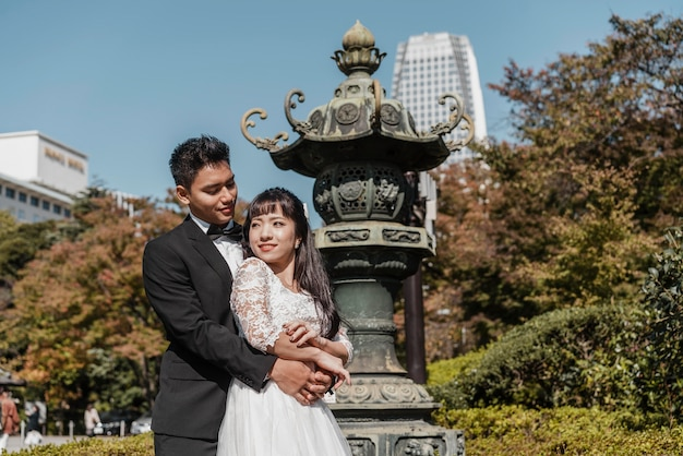 Sposo che abbraccia la sposa all'aperto
