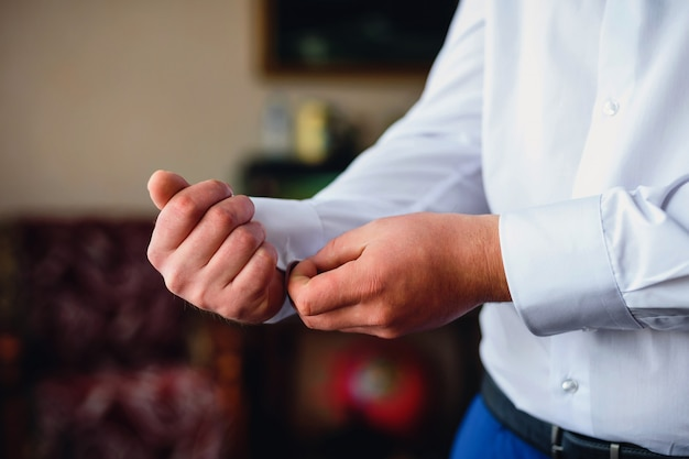 Groom fastens cufflinks on the sleeve of a white shirt.
