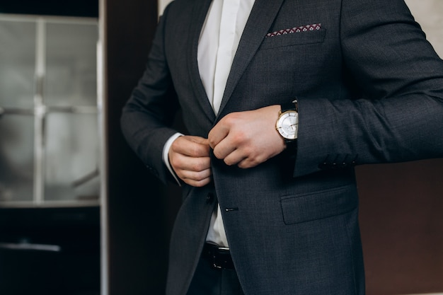 新郎は彼の結婚式のスーツのボタンを締めます