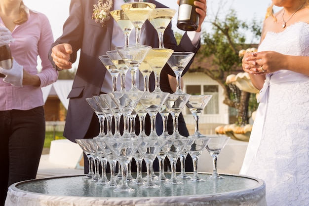 Groom filling a pyramid of glasses with champagne at outdoor garden in wedding ceremony.