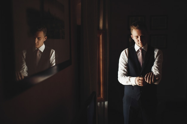 Groom fixes buttons up his cuffs before a window in a little italian house