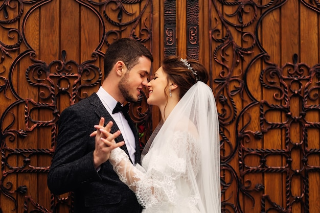 The groom flirts with her beloved woman holding hands on the background of wooden doors