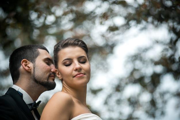 Lo sposo abbraccia dolcemente la sposa con un bouquet da dietro in un parco