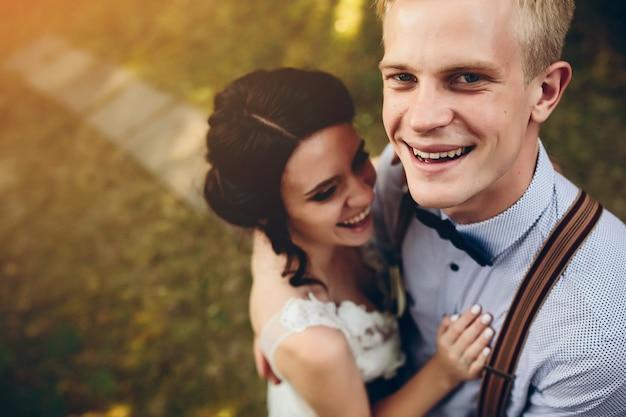 Lo sposo abbraccia delicatamente il suo sposo nella foresta