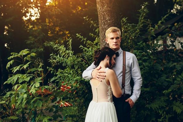 森の中で花嫁を優しく抱きしめる新郎