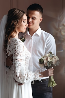 The groom gently hugs the bride in a beautiful boho wedding dress. wedding photo session of the newlyweds.