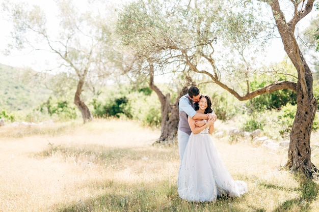The groom gently hugs the bride from behind in the olive grove groom is kissing bride.