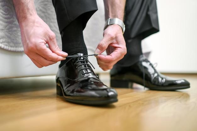 Жених одевается на свадьбу, завязывая шнурки на отполированных стильных черных туфлях.