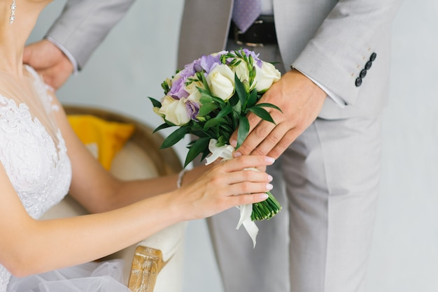 Groom gives the bride a wedding bouquet, a close-up of the hands of a couple in love