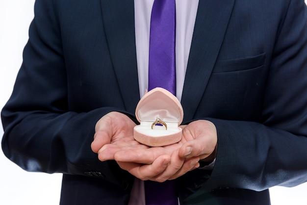 Жених дарит обручальное кольцо в красной коробке