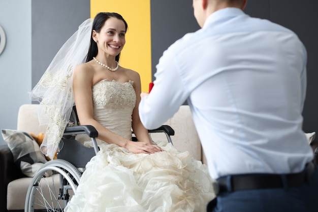 Groom giving ring to bride in wheelchair. wedding for people with disabilities concept