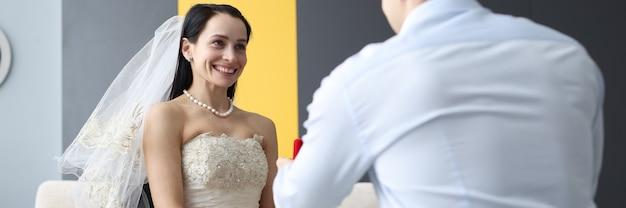 障害を持つ人々の概念のための車椅子の結婚式で花嫁にリングを与える新郎
