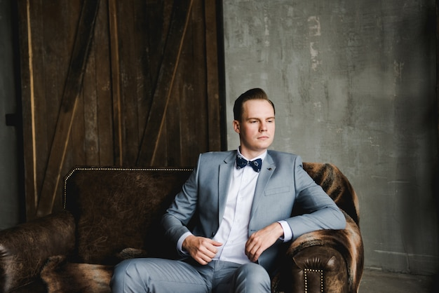 The groom in a gray suit, white shirt and a bow tie is sitting on a brown leather sofa.