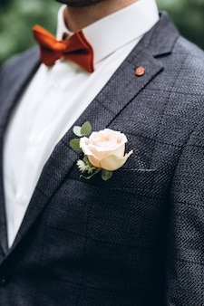 The groom in a grey suit and rose on the lapel of the jacket