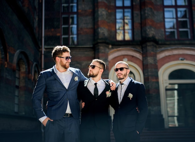 Groom and groomsmen in black sunglasses hold  each other shoulders posing