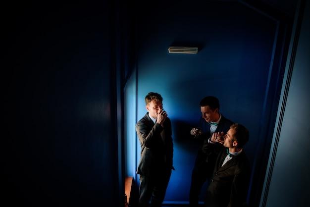 Groom and groomsmen drink whisky standing before a window