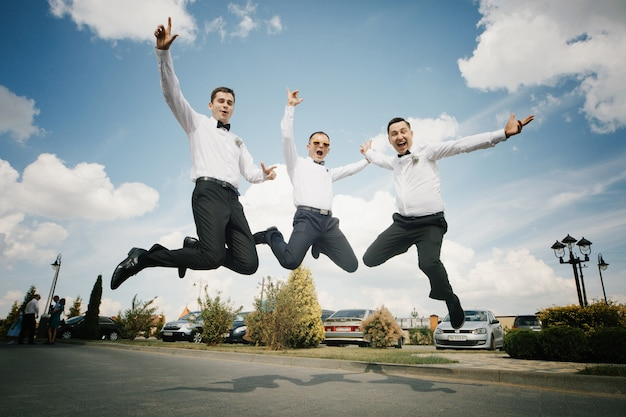 Groom and groomsmen jump up on the path outside